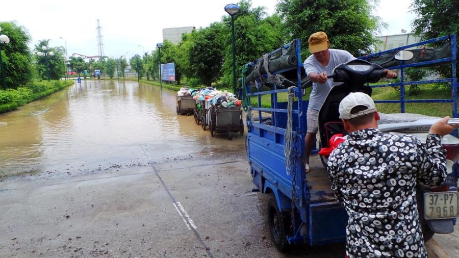 Sáng 26/5, Ban quản lý tòa nhà HH2 đã sử dụng nhiều xe tải để đưa người dân ra khỏi khu vực ngập, kịp giờ đi làm. Một số người dân có xe ba bánh cũng tận dụng cơ hội này để làm thêm.