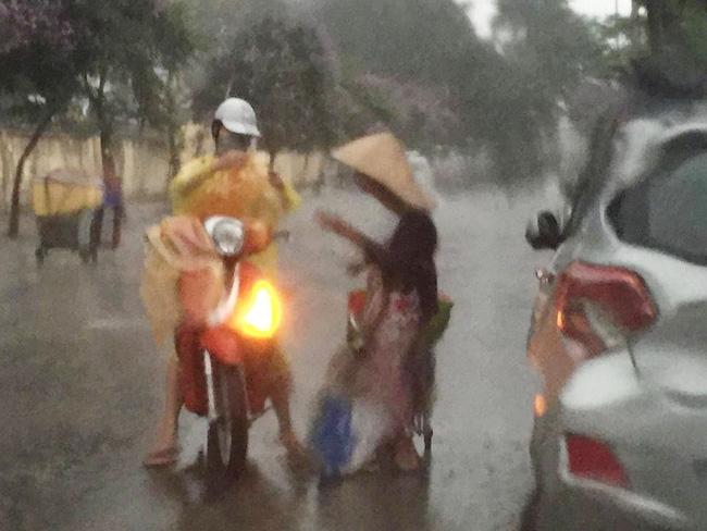 Khoảnh khắc đẹp nhất ngày mưa: Cô gái Hà Nội dừng xe, mặc áo mưa cho cụ bà trong cơn dông - Ảnh 1.
