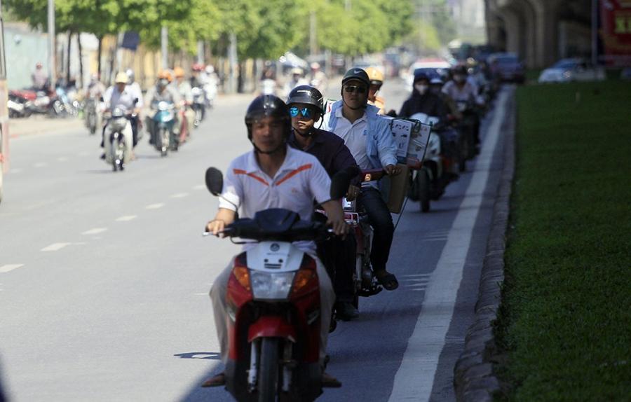 Hàng người đi xe máy nép vào phần đường có bóng râm để tránh nắng trên trục đường Khuất Duy Tiến - Nguyễn Xiển. Hai ngày nay Hà Nội nắng gắt, nhiệt độ ngoài trời có lúc lên đến hơn 40 độ C.