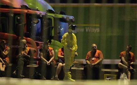 Một nhân viên của đội phá bom và chất độc hóa học trong trang phục bảo hộ bên ngoài văn phòng phân loại bưu kiện Stokke.