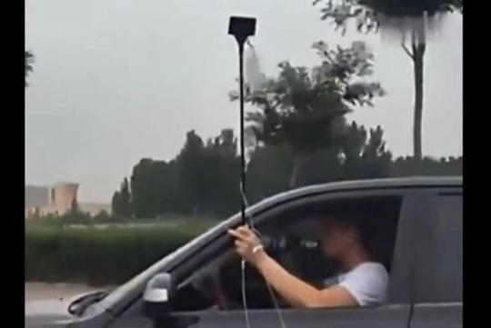 Người đàn ông Trung Quốc vừa lái xe vừa truyền nước và uống bia. Ảnh: UPI