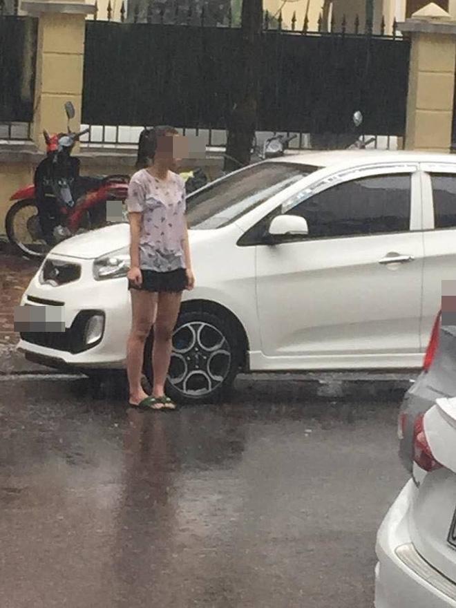 Cô gái đầu trần, đứng dầm mưa giữa phố Hà Nội - Ảnh 1.
