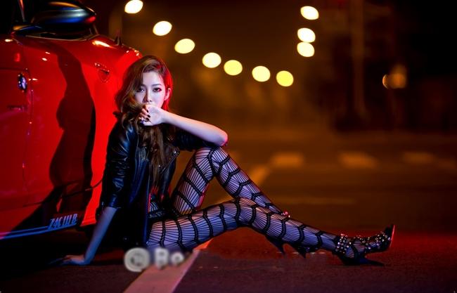 Người đẹp tạo dáng bên chiếc xe sang màu đỏ cáu cạnh
