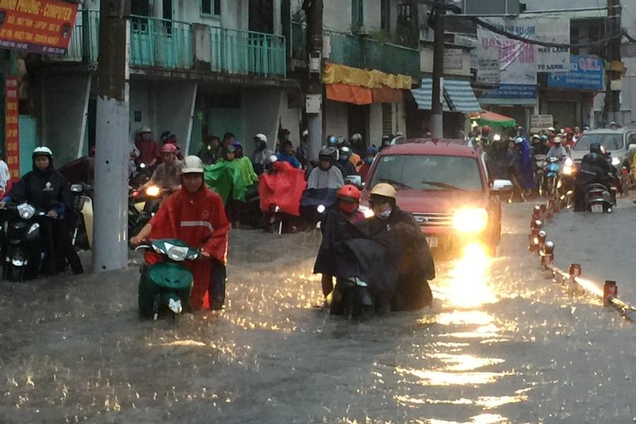 Người dân phải vất vả dầm mưa, lội nước, vượt qua kẹt xe để tìm đường về nhà.