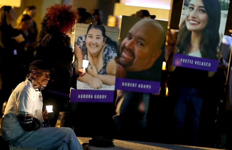 Một người đàn ông ngồi tưởng niệm trước di ảnh của các nạn nhân trong vụ xả súng tại Sở y tế San Bernardino (Ảnh: Getty)