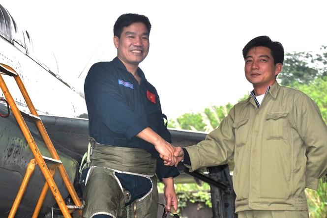 Phi công Nguyễn Hữu Cường (bìa trái, một trong 2 phi công mất tích) được nhân viên kỹ thuật đón xuống sân bay khi kết thúc chuyến bay huấn luyện bằng Mig-21 tại sân bay quân sự Yên Bái, tháng 2.2013 /// Ảnh: Mai Thanh Hải