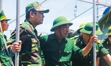 Thiếu tá Nguyễn Hữu Cường (đội mũ cối, giữa) không khỏi căng thẳng khi vừa trở về đất liền.  Ảnh: V.H.