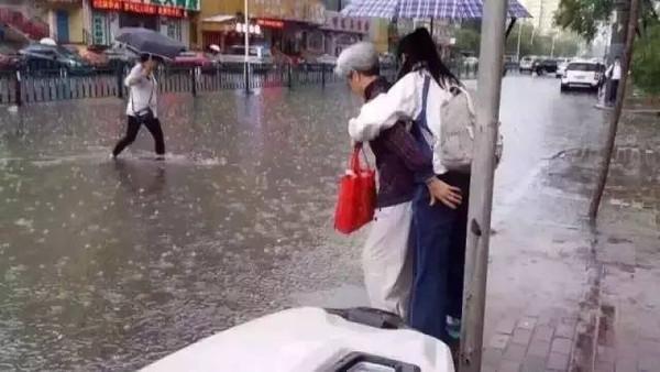 Bức ảnh bà lội nước cõng cháu gái lớn bổng đi học khiến dư luận dậy sóng - Ảnh 1.