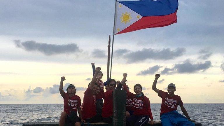 Một nhóm các nhà hoạt động chụp ảnh cùng quốc kỳ Philippines tại bãi cạn Scarborough (Ảnh: AFP)