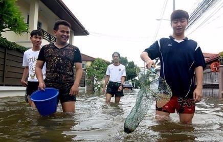 Người dân mang theo lưới vớt cá trên đường phố Bangkok. Ảnh: The Nation