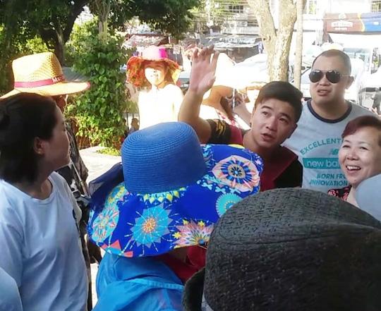 Một người Trung Quốc (giơ tay) từ xe của Công ty Silent Bay bước xuống, giới thiệu cho khách Trung Quốc tham quan tại Tháp Bà (TP Nha Trang) - Ảnh: KỲ NAM