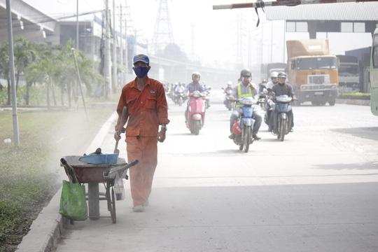 Công nhân nổ lực quét dọn đường trên xa lộ Hà Nội đoạn trạm thu phí cầu Rạch Chiếc nhưng không hiệu quả.