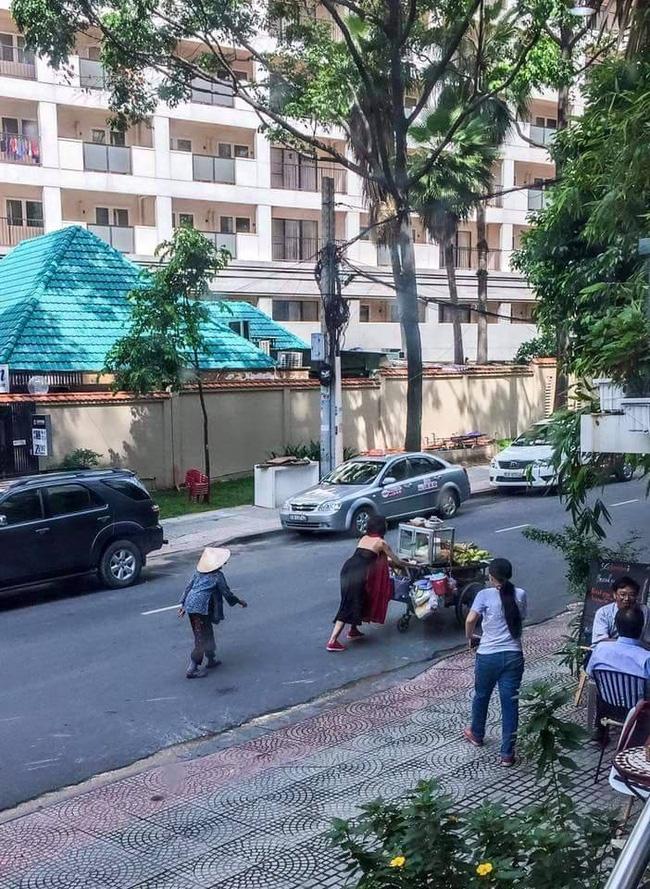 Gặp cô gái váy đen, khăn đỏ đẩy xe cho bà cụ bán rong ở Sài Gòn - Ảnh 1.