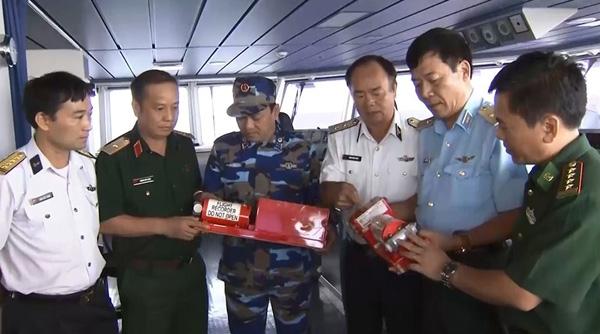 Phó đô đốc Phạm Ngọc Minh (thức ba từ phải sang) và Thiếu tướng Nguyễn Hữu Chí (thứ hai từ phải sang) cùng các cán bộ Sở Chỉ huy trên tàu Cảnh sát biển 8002 xem xét hộp đen vừa được tìm thấy