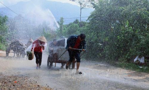 Người dân di dời đến nơi an toàn trong mưa giông. (Ảnh: TTXVN)
