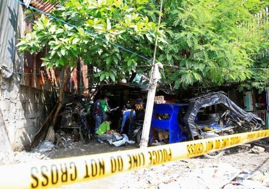 Cảnh sát Quốc gia Philippines (PNP) kiểm tra thi thể của 1 trong 5 kẻ buôn ma túy bị giết hôm 3-7 ở Manila. Ảnh: REUTERS