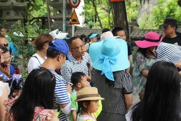 Một người Trung Quốc (đeo kính) không biết có hiểu gì về văn hóa, lịch sử Việt Nam không nhưng đang thao thao giới thiệu cho đoàn khách Trung Quốc ở chùa Long Sơn, TP Nha Trang, lúc 11h25, ngày 5/7 - Ảnh: Viết Hảo