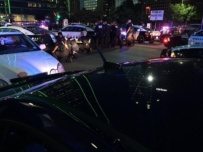 Cảnh sát Dallas nấp sau các xe ô tô tại khu thương mại Lamar để vây bắt kẻ tình nghi (Ảnh: Telegraph)