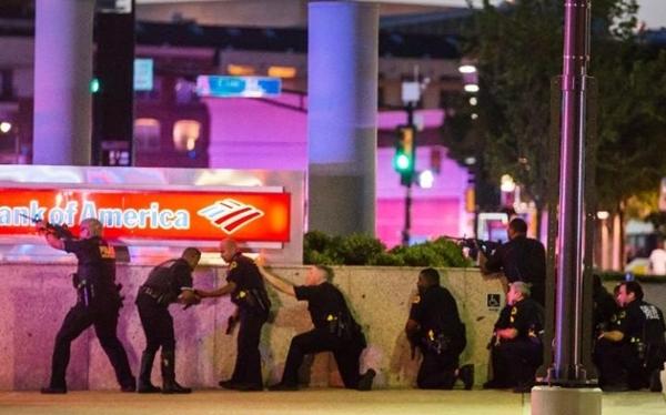 Cảnh sát Dallas nấp vào góc khuất sau khi có tiếng súng vang lên. Ảnh: Dallas Morning News.
