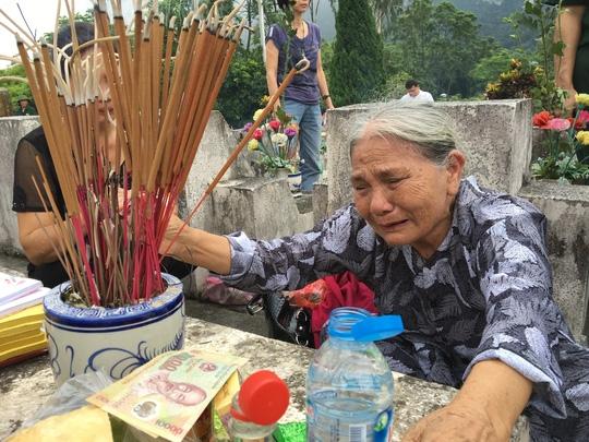 Bà Nguyễn Thị Đạo, 83 tuổi, mẹ của liệt sĩ Nguyễn Văn Thịnh - chiến sĩ Đại đội 11, Tiểu đoàn 9, Trung đoàn 149, Sư đoàn 356 - bên bia mộ của con trai mình tại nghĩa trang liệt sĩ Vị Xuyên sáng 12-7. Ảnh: Văn Duẩn