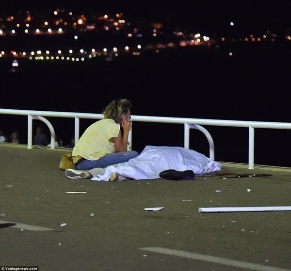 Một phụ nữ ngồi bên cạnh thi thể người thân thiệt mạng trong vụ tấn công khủng bố Nice. Ảnh: Vantage News.