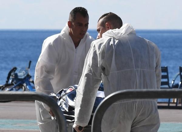 Nhân viên pháp y Pháp đưa một thi thể ra khỏi hiện trường. Ảnh: AFP.