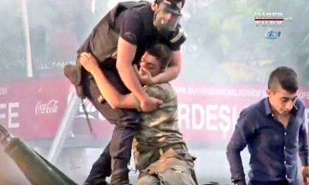 Hình ảnh cảnh sát Thổ Nhĩ Kỳ ôm lính đảo chính bị người dân ném đồ vật và giẫm đạp gây xúc động. Ảnh chụp từ clip.
