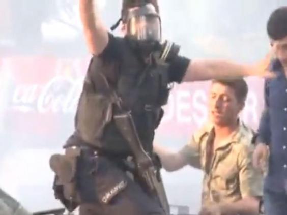 Viên cảnh sát giơ tay kêu gọi đám đông bình tĩnh (Ảnh chụp từ clip)