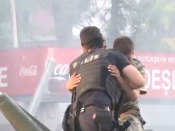 Sau đó viên cảnh sát giang tay ôm người lính để bảo vệ anh này (Ảnh chụp từ clip)