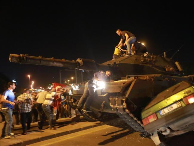 Xe tăng đảo chính nghiến nát ô tô. (Ảnh: AFP)