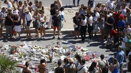 Người dân đứng quanh khu vực đặt hoa tưởng niệm các nạn nhân thiệt mạng trong vụ tấn công khủng bố ở Nice.