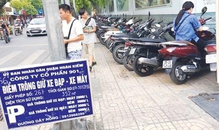 Bảng niêm yết giá công khai, nhưng chiều qua nhân viên điểm trông xe tại vỉa hè phố Hàng Bài vẫn thu giá gần gấp đôi quy định. Ảnh: AT.