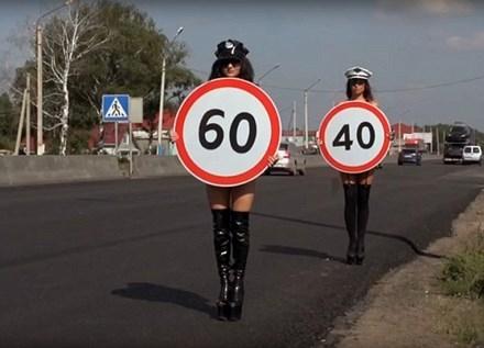 Các cô gái cầm biển báo hạn chế tốc độ trên đường.