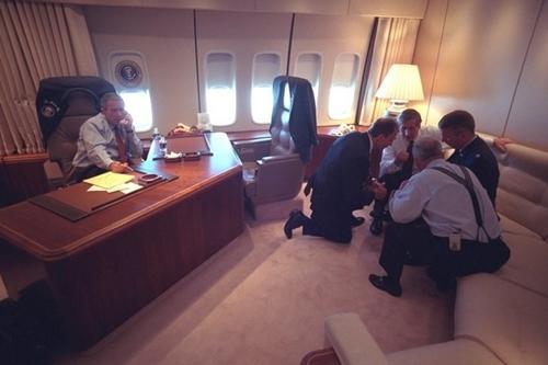 Tổng thống Bush nói chuyện qua điện thoại trong khi các nhân viên cấp cao bàn thảo trong văn phòng của ông trên chuyên cơ Không lực số Một.