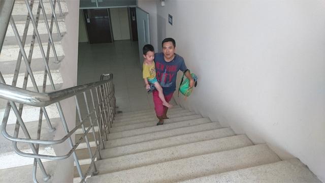 Anh Du vất vả bế con leo cầu thang bộ lên tầng 8.