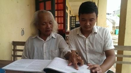 Ông Nguyễn Ngọc Đoán - một thợ cối đang giải thích một số từ lóng cho cậu cháu nội. Ảnh: Nhã Khanh