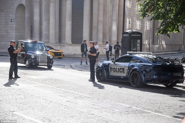 Hai cảnh sát chụp ảnh với Ford Mustang