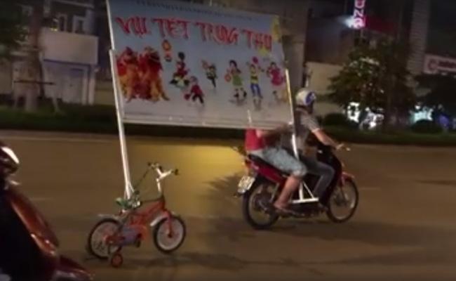 Clip: Hai nam thanh niên tận dụng xe đạp trẻ em để vận chuyển biển hiệu trên đường phố Hà Nội - Ảnh 2.