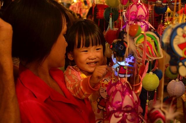 Một em nhỏ thích thú khi được tự tay chọn món lồng đèn yêu thích