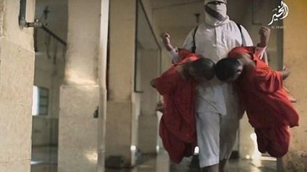 Tên đao phủ trong trang phục màu trắng, tay xách hai tù nhân đưa vào lò mổ. Ảnh: Daily Mail