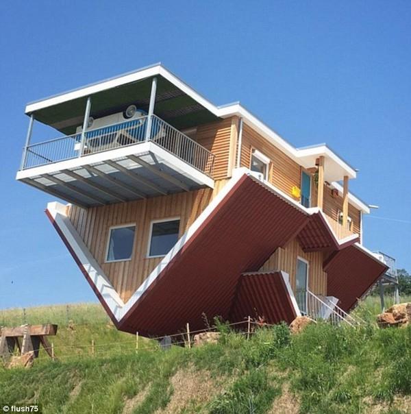 Bên ngoài căn nhà với thiết kế lộn ngược. Một chiếc xe ô tô cũng được thiết kế treo ngược bên ngoài căn nhà