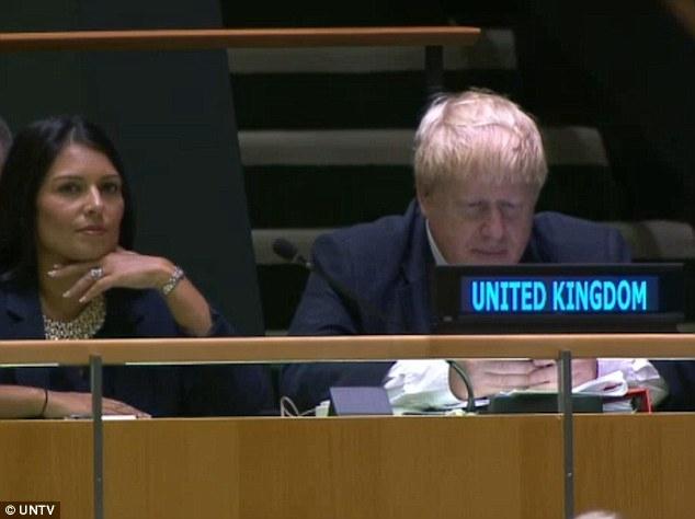 Ngoại trưởng Anh Borish Johnson (phải) dán mắt vào điện thoại trong lúc Thủ tướng Theresa May phát biểu tại Đại hội đồng Liên Hợp Quốc (Ảnh: UNTV)