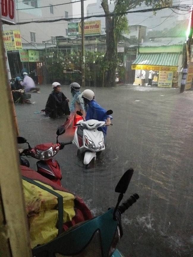 Người mẹ hớt hải lội nước ngập tìm con bị thất lạc trong trận mưa kinh hoàng ở Sài Gòn - Ảnh 2.