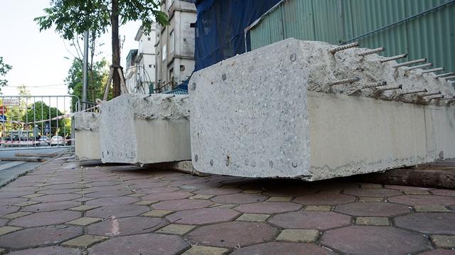Từng khúc dầm bê tông được vận chuyển bằng cẩu trục tháp xuống đất.
