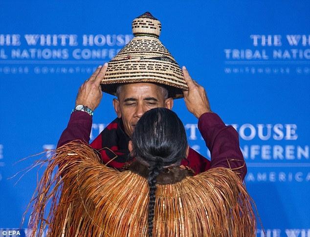 Chủ tịch Hội các bộ tộc của Mỹ Brian Cladoosby đã đội mũ và choàng áo cho tổng thống trước sự chứng kiến của các đại biểu tham dự hội nghị. (Ảnh: EPA)