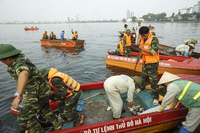 Liên tục hàng trăm lượt xuồng máy ra vào vận chuyển xác cá ra khỏi lòng hồ.