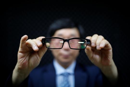 Ông Moon Seoung-ok khoe mắt kiếng có gắn máy quay lén Ảnh: REUTERS