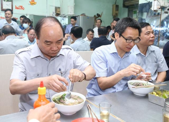 Thủ tướng Nguyễn Xuân Phúc dùng bữa sáng và uống cà phê tại một quán phở trên đường Nguyễn Hậu, phường Tân Thành, quận Tân Phú. (Ảnh: Thống Nhất - TTXVN)