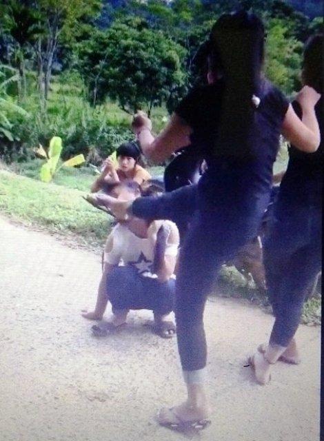 Cô gái trẻ mặc áo trắng bị đá thẳng vào mặt (ảnh cắt từ clip)