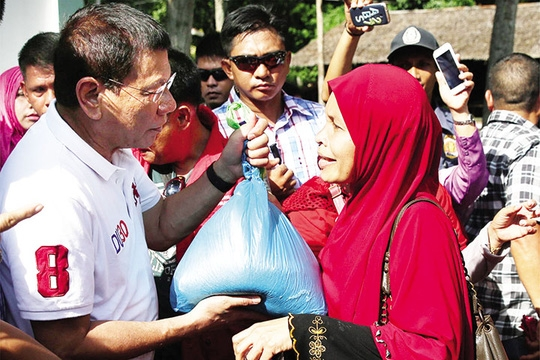Tổng thống Duterte phát hàng viện trợ cho người dân trong chuyến thăm tỉnh Basilan hồi tháng 7. Ảnh: PPD